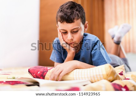 Studio portrait of a schoolboy reading a textbook while lying in bed - stock photo