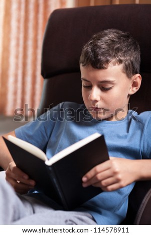 Studio portrait of a schoolboy reading a textbook while sitting on an armchair - stock photo