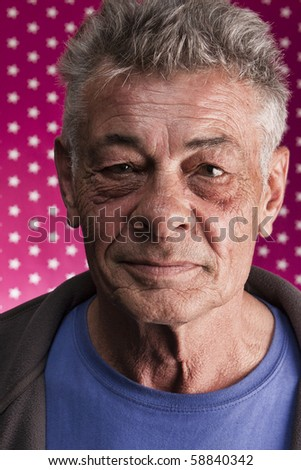 Studio portrait of a senior male smiling in front of a pink background with white stars. - stock photo