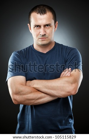 Studio portrait of a serious young man in t-shirt - stock photo