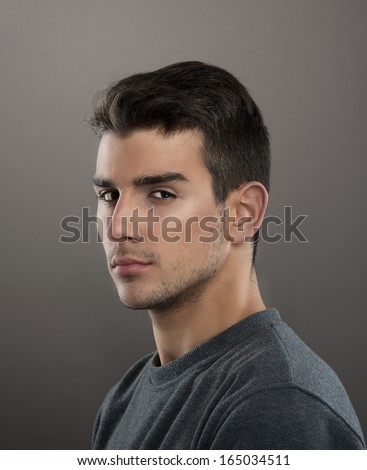 Studio portrait of a serious young man looking at camera, gray background  - stock photo