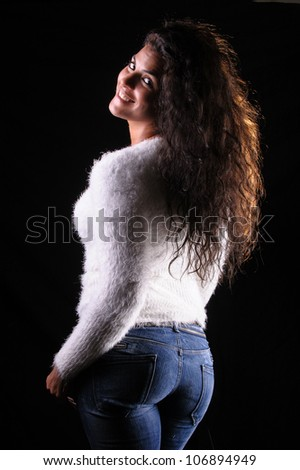 studio portrait of a sexy brunette woman wearing a white jersey and jeans - stock photo