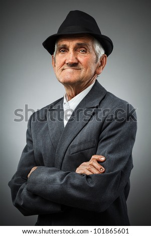 Studio portrait of a smiling old man with hat - stock photo