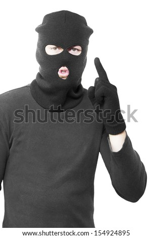 Studio Portrait Of A Sneaky Male Criminal Committing A Silent Crime While Gesturing For Quiet Or Pointing Up To Blank Copyspace, Isolated On White Background