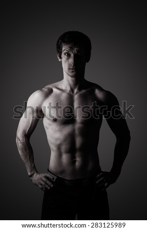 Studio portrait of a sporty young man in low key - stock photo