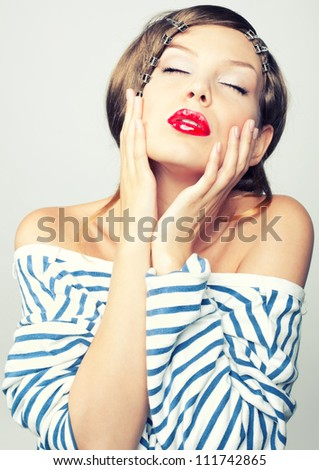Studio portrait of a sweet girl with red lips in a vest - stock photo