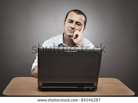 Studio portrait of a thoughtful businessman at his laptop - stock photo