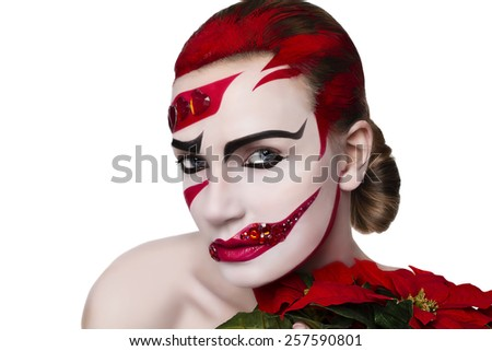 Studio portrait of a woman. Art make-up in red. Girl with red flower in hand. On a white background - stock photo