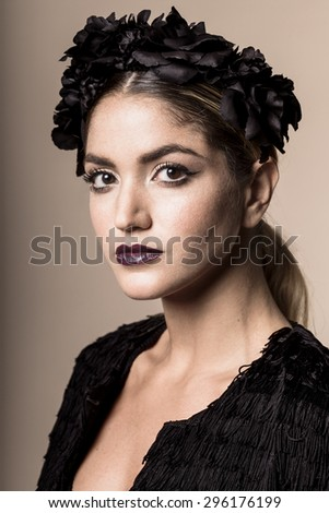 Studio portrait of a young and classy attractive woman wearing black attire and a faux black flower crown.
