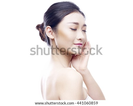 studio portrait of a young asian woman, hand on chin, eyes closed, side view, isolated on white.
