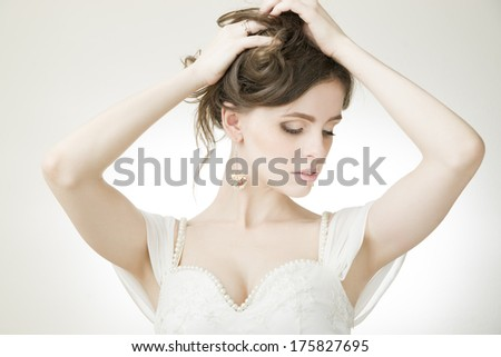 Studio portrait of a young beautiful bride in a white dress. Professional make-up and hairstyle. - stock photo
