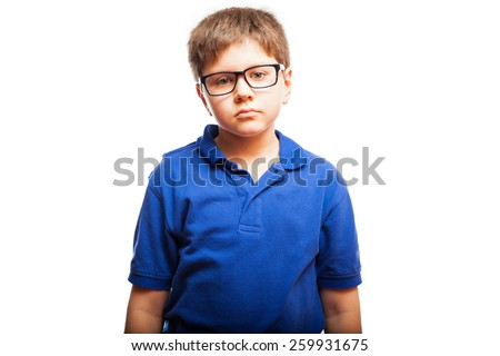 Studio portrait of a young boy with glasses and a blank expression - stock photo