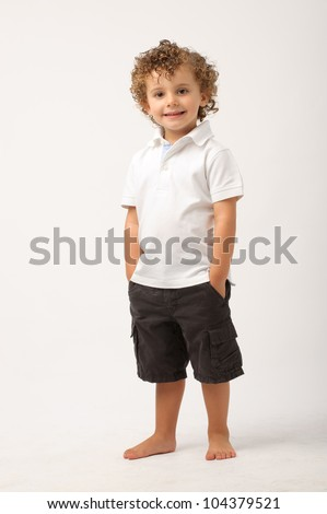 studio portrait of a young boy with his  hands on his pockets - stock photo