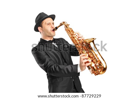 Studio portrait of a young man wearing hat and playing on saxophone isolated on background - stock photo