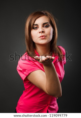 Studio portrait of a young redhead lady blowing kisses, over gray background - stock photo