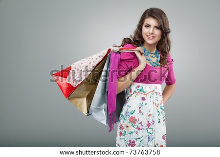 studio portrait of a young woman in a colourful outfit, holding in one hand three shopping bags. she is laughing and looking very happy. - stock photo