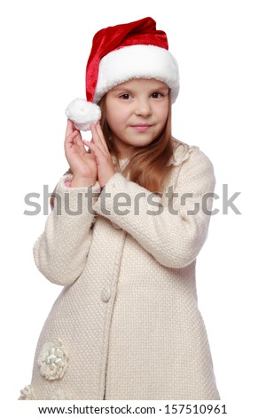 Studio portrait of adorable happy little girl with long beautiful hair with a Santa hat isolated on white/Christmas portrait of a cute child in a Santa's hat