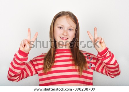 Studio portrait of adorable little girl of 8-9 years old, wearing coral color stripes pullover, standing against white background, showing peace sign - stock photo