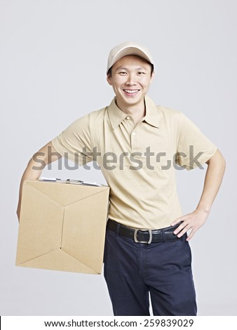 studio portrait of an asian delivery man smiling. - stock photo