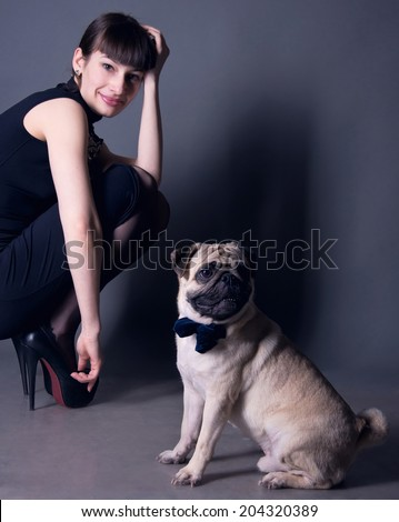 Studio portrait of an elegant pug dog gentleman wearing blue bow tie and sitting on the floor, with his owner beautiful young woman model sitting behind. Gray background, copy space - stock photo