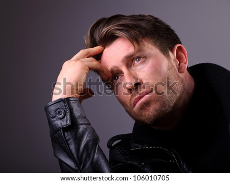 studio portrait of an handsome man thinking ans worried - stock photo