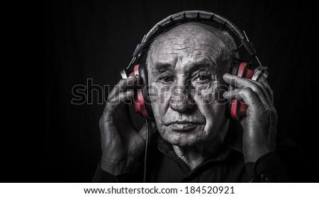 Studio portrait of an old man in headphones - stock photo