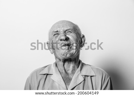 studio portrait of an old man with a toothache - stock photo