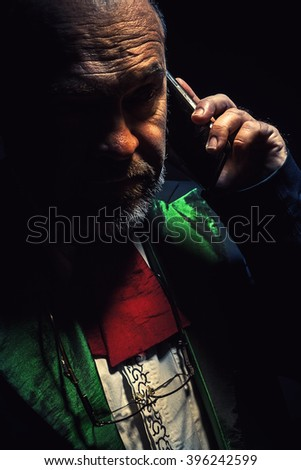 Studio portrait of an older beard man, looks like an artist, conductor or something similar.  - stock photo