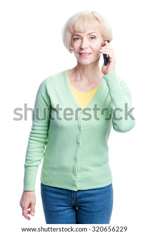 Studio portrait of attractive blond middle age woman talking by smartphone. Isolated on white. - stock photo