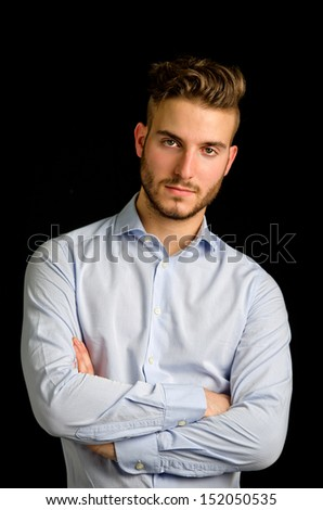 Studio portrait of attractive young businessman looking in camera, on black background - stock photo