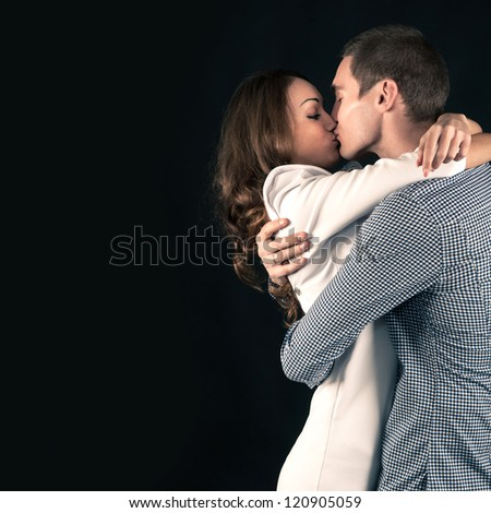 Studio portrait of attractive young couple on black background with copy space. - stock photo