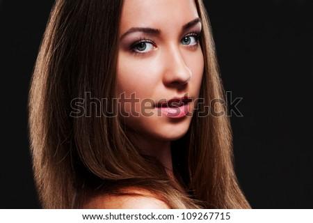 studio portrait of attractive young woman over dark background - stock photo