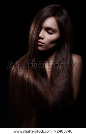 studio portrait of attractive young woman with long hair - stock photo