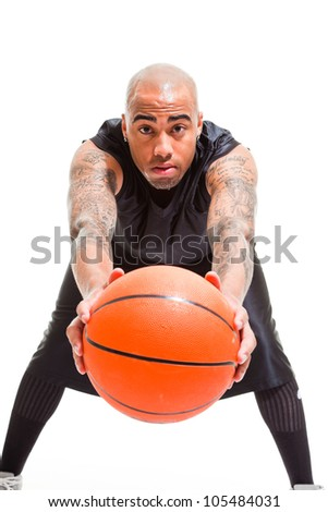 Studio portrait of basketball player standing and holding ball isolated on white. Tattoos on his arms.