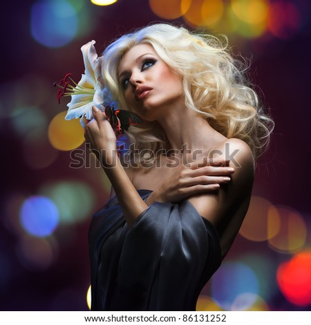 studio portrait of beautiful blonde and tropical butterfly sitting on her hand on dark red background - stock photo