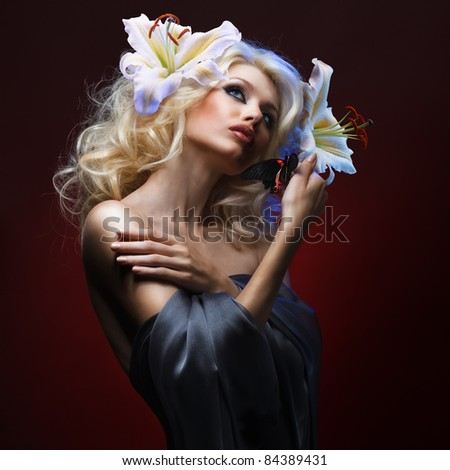 studio portrait of beautiful blonde with blue eyes wearing flowers in her hair and tropical butterfly sitting on her hand on dark red background