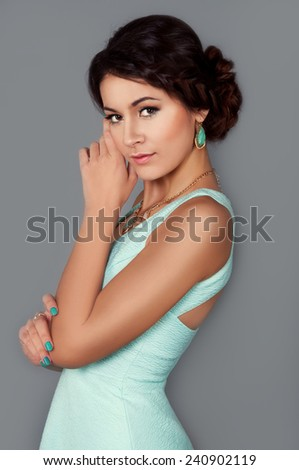 Studio portrait of beautiful brunette in teal dress with turquoise earrings - stock photo