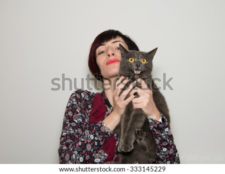 Studio portrait of beautiful girl with funny chartreux cat - stock photo