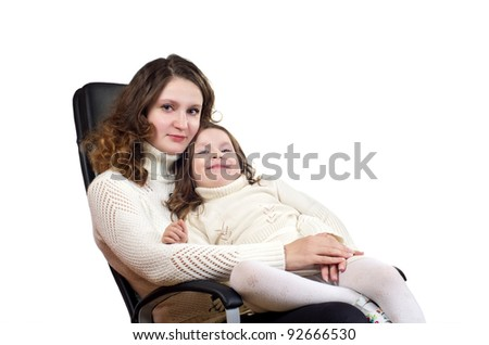 Studio portrait of beautiful little girl and her mother sitting on black leather armchair. Isolated on white background.