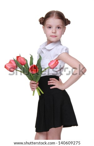 Studio portrait of beautiful sweet little schoolgirl holding red tulips