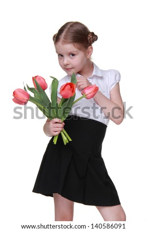 Studio portrait of beautiful sweet little schoolgirl holding red tulips on Holiday concept theme/Cheerful schoolgirl wearing white blouse and black skirt and holding bouquet of flowers on Mothers Day