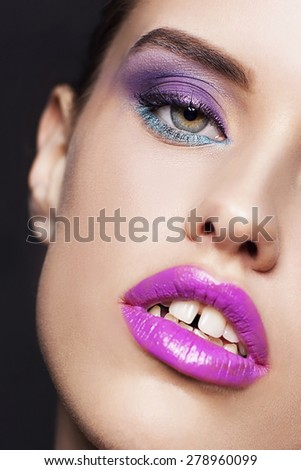 Studio portrait of beautiful woman with professional make up on black background