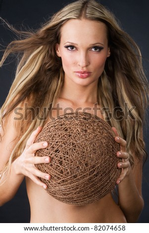 Studio portrait of beautiful woman with skein of thread