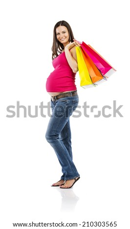 Studio portrait of beautiful young pregnant woman with shopping bags, isolated on white background - stock photo