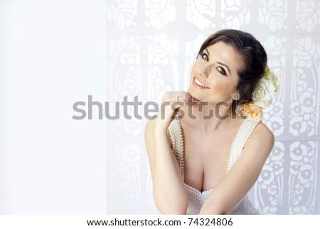 Studio portrait of beauty bride in white elegant dress with purls - stock photo