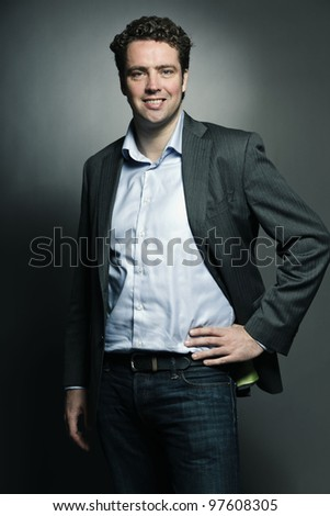 Studio portrait of business man isolated on grey background - stock photo