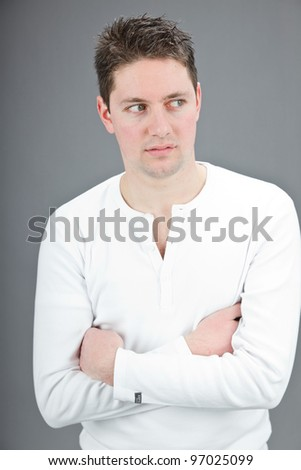 Studio portrait of casual expressive young man brown short hair wearing white shirt isolated on grey background