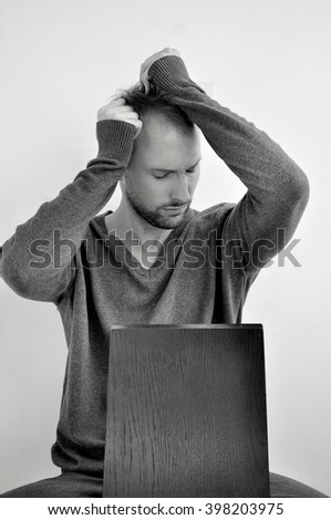Studio portrait of caucasian bearded young man. With facial expression, closed eyes, passionate. Sitting on chair, touching his face with  hands. Posing. Test shot - stock photo