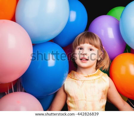 Studio portrait of Caucasian blond little girl with colorful balloons on black - stock photo