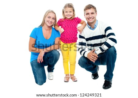 Studio portrait of charming young family. Parents in squatting posture with daughter standing in between